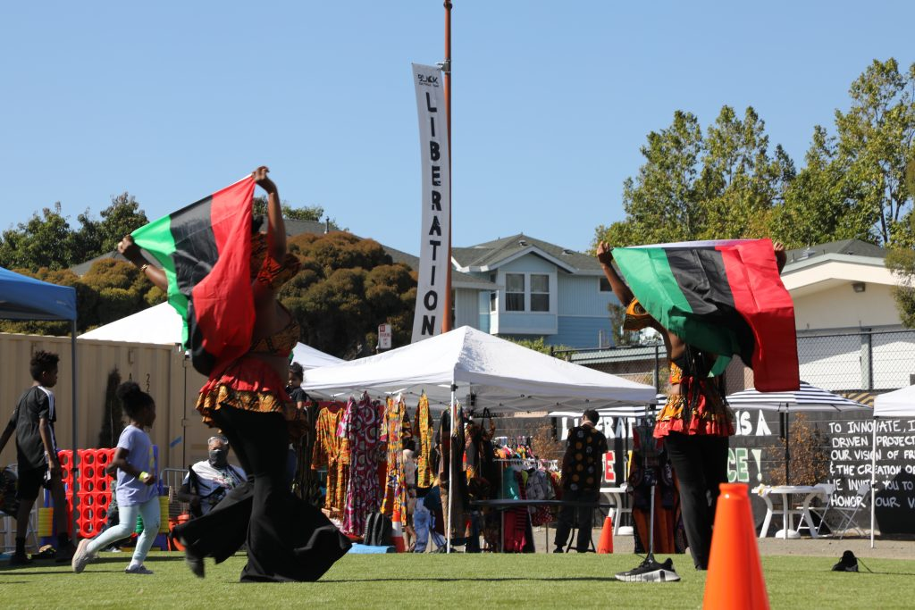 """Two dancers with large green, black, red flags and a banner that says """"LIBERATION"""" in the background"""