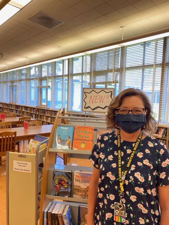 A woman wearing glasses and a mask stands inside a school library.