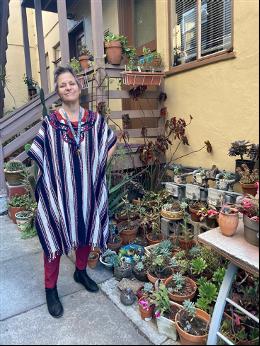 A woman wearing a striped poncho smiles outside