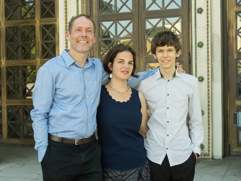 A man, woman, and teen son stand in front of an Oakland historic-looking building.